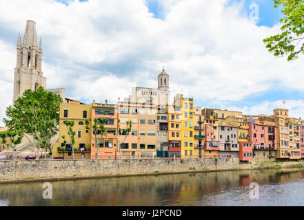 Banks of the River Onyar with the Basilica de Sant Feliu and Cathedral belltower towering over the old town hanging - Stock Photo
