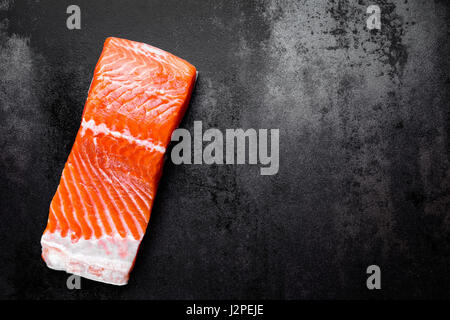 Raw salmon or trout sea fish fillet on black metal background, top view - Stock Photo