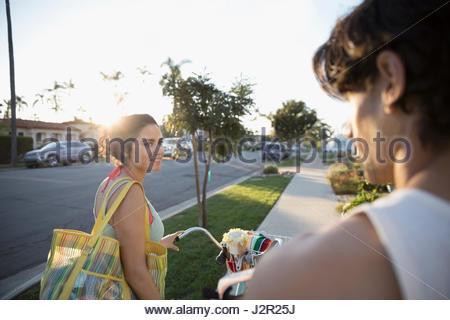 Couple walking beach cruiser bicycles on summer sidewalk - Stock Photo