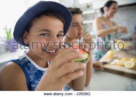 Portrait smiling boy eating watermelon in kitchen - Stock Photo