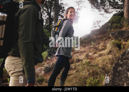 Young woman with her boyfriend on walk through countryside. Happy young couple hiking together. - Stock Photo