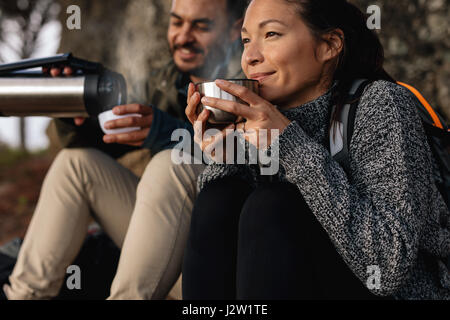 Young couple taking a break on a hike. Man and woman drinking coffee while out hiking. - Stock Photo