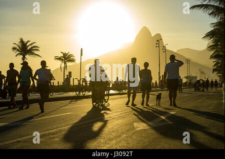 RIO DE JANEIRO - FEBRUARY 12, 2017: Silhouettes of Brazilians stroll along the beachfront Avenida Vieira Souto street - Stock Photo