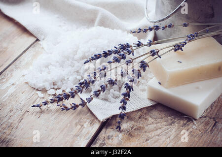 Natural soap, lavender, salt, cloth, old cans on a wooden board, rustic hygiene items for bath and spa. - Stock Photo