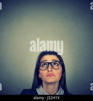 Young skeptical woman looking up isolated on gray wall background with copy space above head. Human emotions, feelings - Stock Photo
