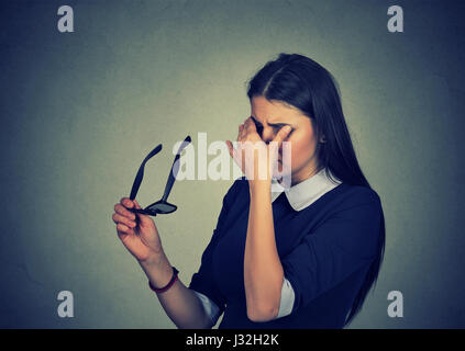 Woman with glasses rubbing her eyes feels tired isolated on gray wall  background. Young girl suffering from eye - Stock Photo