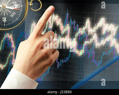 Candlestick chart graphic and black compass in light - Stock Photo