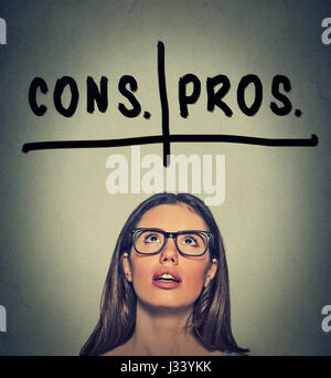 pros and cons, for and against argument concept. Young business woman with glasses looking up deciding isolated - Stock Photo