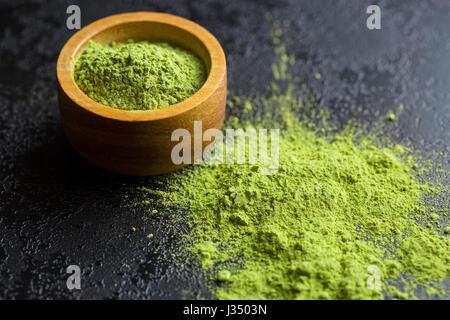 Green matcha tea powder in bowl. - Stock Photo