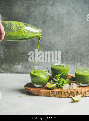 Fresh smoothie pouring from bottle to glasses, copy space - Stock Photo