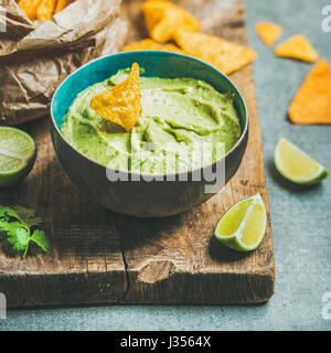 Fresh guacamole sauce in blue bowl and chips, square crop - Stock Photo
