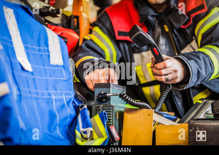 Firefighter used a radio set in a fire engine - Stock Photo
