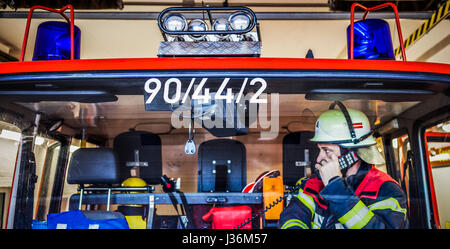Firefighter used a radio set in a fire truck - Stock Photo