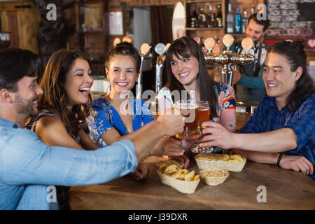 Happy friends toasting beer glasses in restaurant - Stock Photo