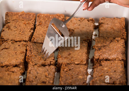Delicious brown colored chocolate brownies lined up, square pieces as seen from above angle, metal cake cutter being - Stock Photo