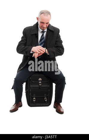 Middle age business man checking time sitting on carry on luggage isolated on white background - Stock Photo