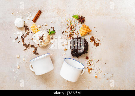 Scoops of ice cream in a variety of delicious and ingredients with two enamel mugs, flat lay - Stock Photo