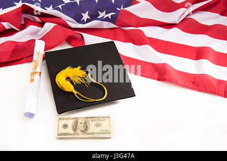 Close-up view of graduation mortarboard, diploma, dollar banknotes and us flag on white, education loan concept - Stock Photo
