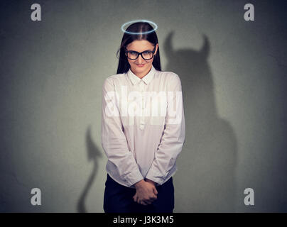 Shy quiet angel woman with devil character - Stock Photo