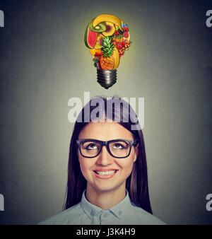 Eating healthy diet tips concept. Headshot of a woman looking up at light bulb made of fruits isolated on gray wall - Stock Photo