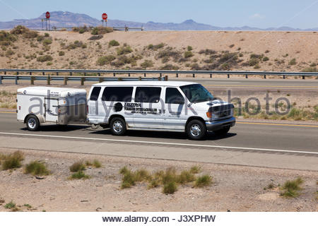 Small van pulling trailer on I-10 in southwestern New Mexico, Shuttle service by Loyola - Stock Photo
