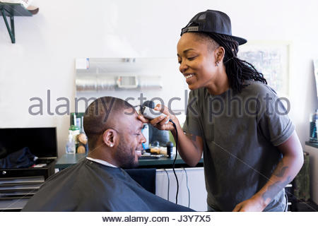 Female barber using hair clippers on male customer in barber shop - Stock Photo