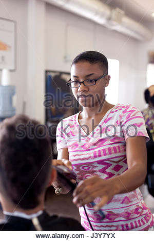 Female barbers using hair clippers on boy in barber shop - Stock Photo