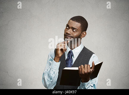 Closeup portrait confused, unhappy serious man holding, reading  book, having many questions, thinking, isolated - Stock Photo