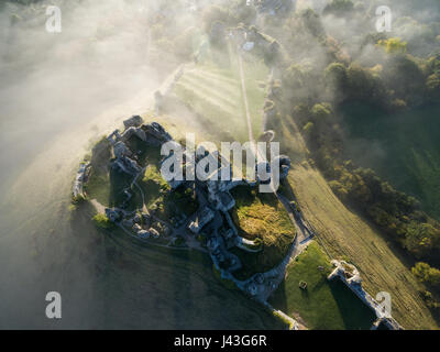 Aerial view of Corfe Castle at Sunrise on a misty morning - Stock Photo