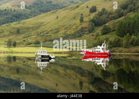 Boats reflecting on Loch Lochy - Stock Photo