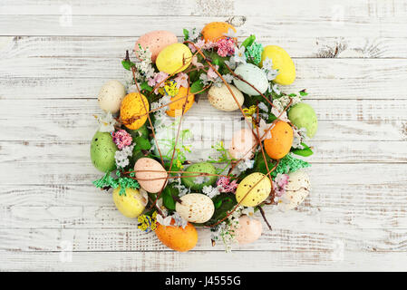 Decoration from easter eggs in shape of circle on painted wooden background - Stock Photo