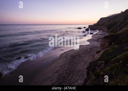 Malibu California pacific ocean dusk at El Matador State Beach. - Stock Photo