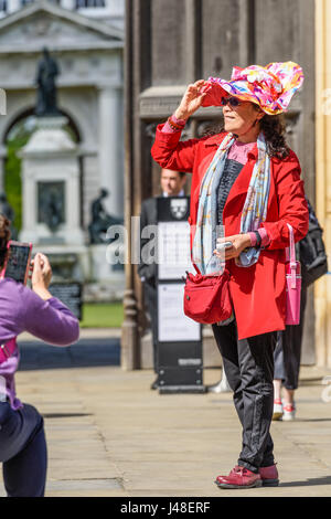 A female chinese tourist, with a red coat and bag and a flowery hat, poses for a photograph in front of the main - Stock Photo
