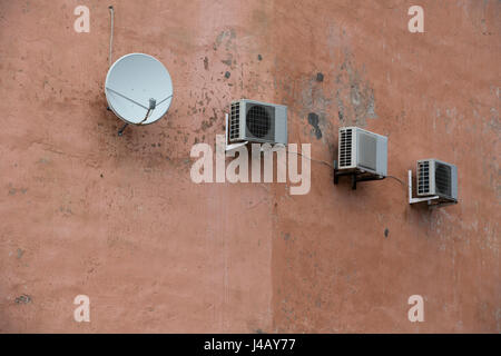 Air compressors of the air conditioner on the vintage wall, with satelite antena. - Stock Photo