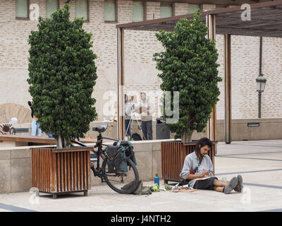 artist artists working drawing painting sketching easels open air sitting floor ground standing a an easel bicycle - Stock Photo