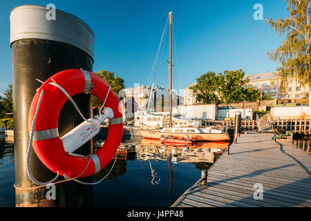 Riga, Latvia - July 1, 2016: Lifebuoy Hanging On A Pole Near City Pier Harbour Bay And Quay In Summer Sunny Evening. - Stock Photo