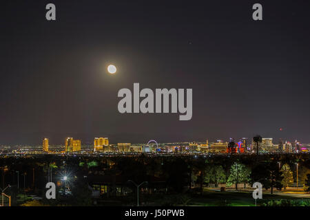 Las Vegas, Nevada, USA - May 13, 2017:  Moon rising over the lights of the Las Vegas strip in Southern Nevada. - Stock Photo
