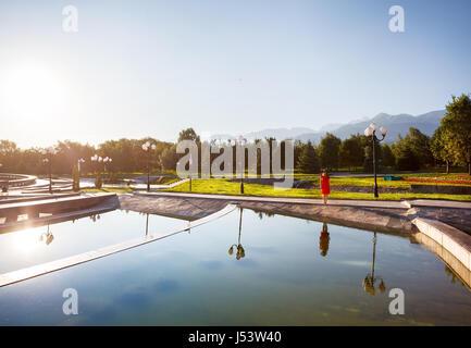 Woman in orange dress near fountain at sunrise in the famous park of Almaty, Kazakhstan - Stock Photo