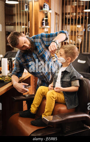 Pleasant bearded barber doing his job - Stock Photo