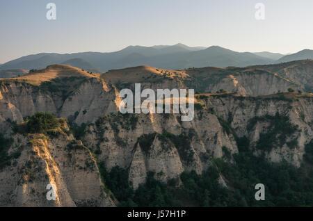 Morning light over Sand Pyramids near Melnik with Pirin Mountains in the horizon, Bulgaria. - Stock Photo