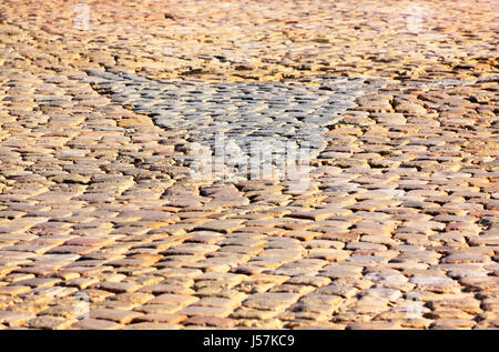 Granite dichromatic cobblestone pavement detail with triangle shape and limited DOF in warm morning light - Stock Photo