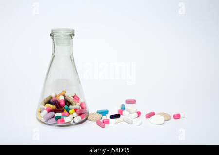 Colorful medical pills in a glass container and scattering on white background. - Stock Photo