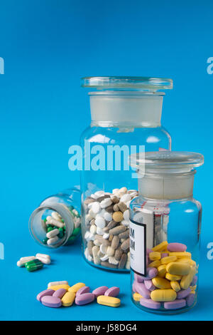 Colorful medical pills in a glass container and scattering on a blue background. - Stock Photo