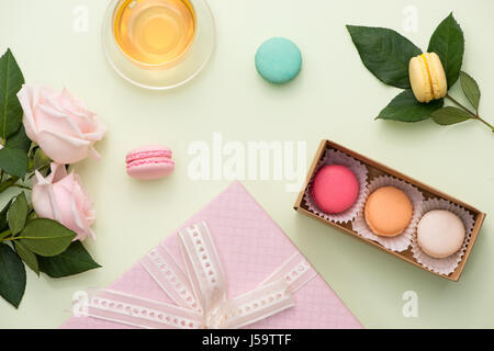 French macaroons. Many variegated sweet macarons in box with bouquet of pink roses on the table - Stock Photo