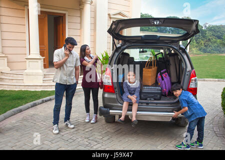 Family standing near car to go on vacation - Stock Photo