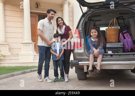 Family standing beside open boot of parked car to go on vacation - Stock Photo