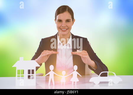 family in white paper with a woman in the background against grass under a sunny sky - Stock Photo