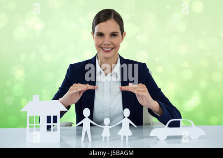 family in white paper with a woman in the background against green abstract light spot design - Stock Photo