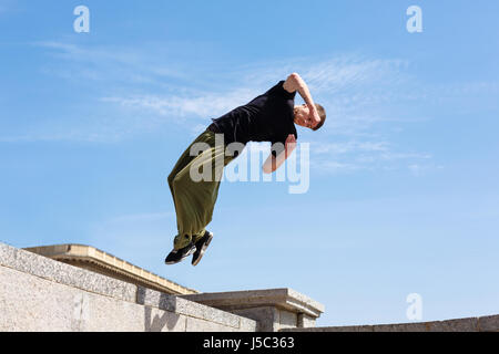 Young man doing a back flip with a turn. Parkour in the urban space. Sports in the city. Sport activity. - Stock Photo