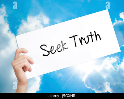 Seek Truth Sign on white paper. Man Hand Holding Paper with text. Isolated on sky background.  technology, internet - Stock Photo